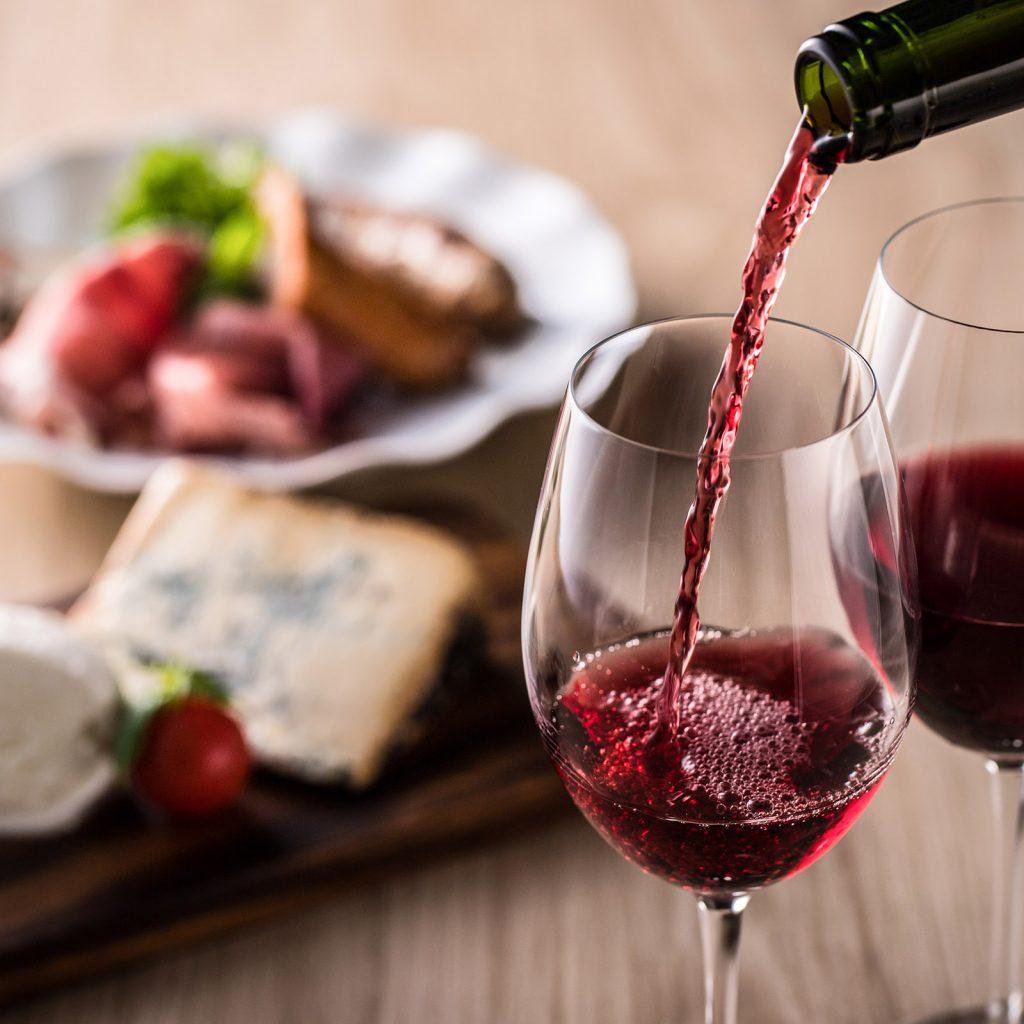 glas dat gevuld wordt met rode wijn en passende hapjes en drankjes die aansluiten op de smaak.